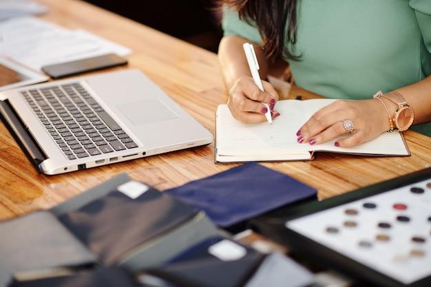 Close-up beeld van vrouwelijke atelier eigenaar aan tafel zitten met geopende laptop en schrijven in planner