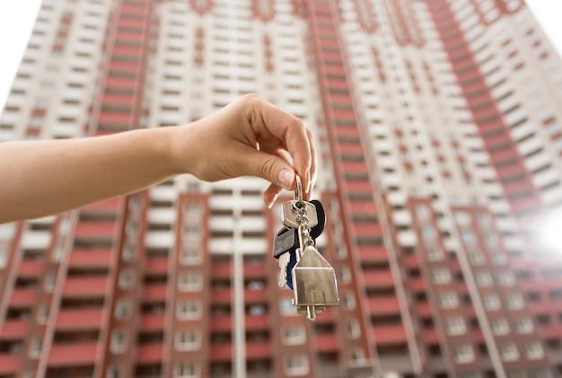 Close-up beeld van vrouwelijke hand met sleutels van nieuw appartement tegen hoog gebouw