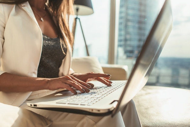 Close-up beeld van vrouwelijke handen typen op laptop toetsenbord in moderne kantoren.