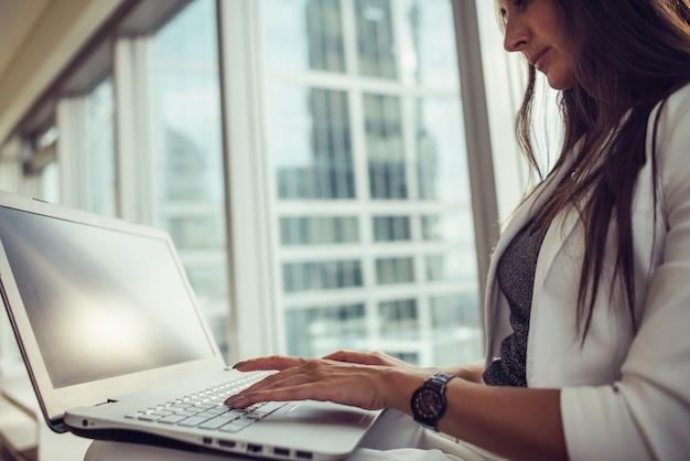 Close-up beeld van vrouwelijke handen vrouw die op laptop in kantoor werkt.