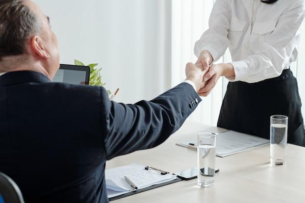 Close-up beeld van vrouwelijke sollicitant die de hand van de ceo van het bedrijf schudt voor een belangrijk sollicitatiegesprek