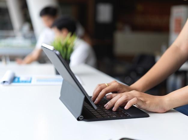 Close-up beeld van vrouwelijke typen op tablet toetsenbord tijdens het werken aan haar project met haar collega op de achtergrond
