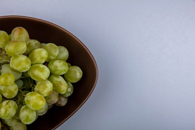 Close-up beeld van witte druif in kom op grijze achtergrond met kopie ruimte