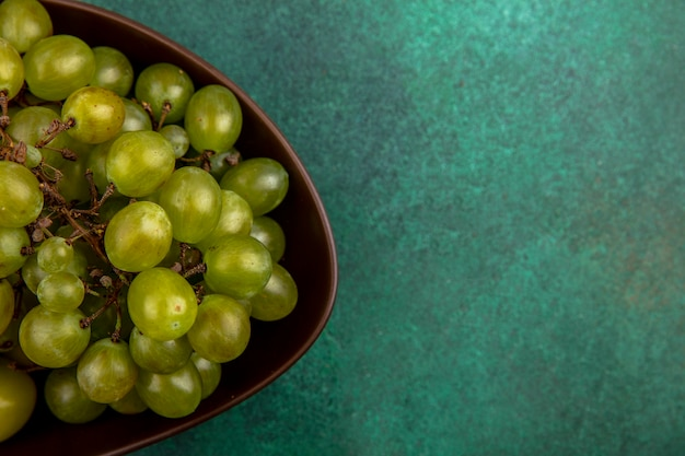 Close-up beeld van witte druif in kom op groene achtergrond met kopie ruimte
