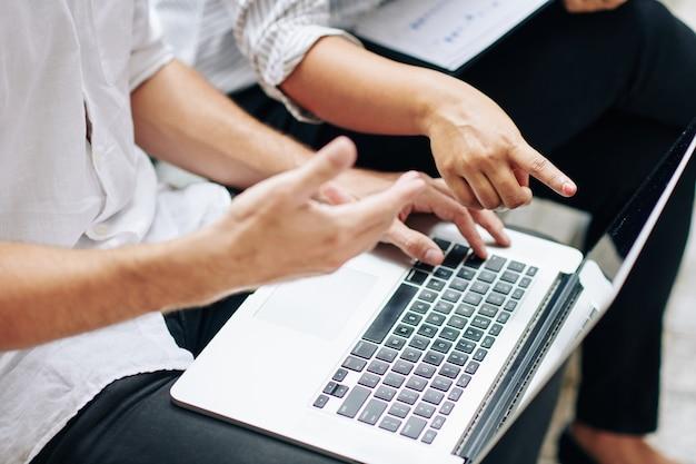 Close-up beeld van zakenmensen die verslag bespreken en gegevens analyseren op het laptopscherm