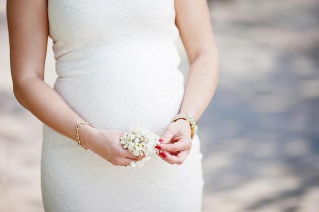 Close-up beeld van zwangere vrouw haar buik met handen aan te raken