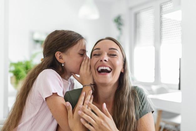 Close-up beeld verbaasde moeder hoort ongelooflijk nieuws van dochtertje, meisje deelt geheim iets interessants te vertellen terwijl moeder open mond verrast voelt, vertrouwen, vertrouweling, leuk concept