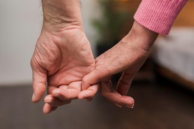 Close-up bejaarde echtpaar hand in hand