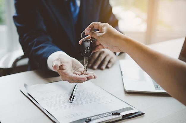 Close-up bekijken hand van agent autosleutel geven aan klant na ondertekende huurcontract formulier.