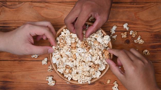 Close-up bekijken multiculturele vrienden popcorn eten.