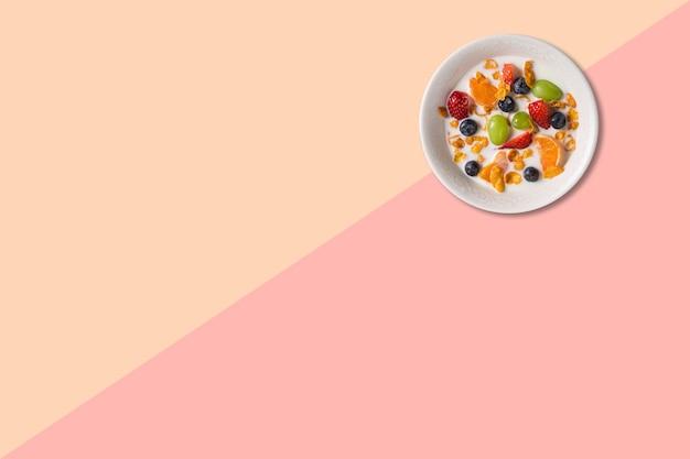 Close-up bekijken verschillende vruchten soep met melk geïsoleerd op roze achtergrond.