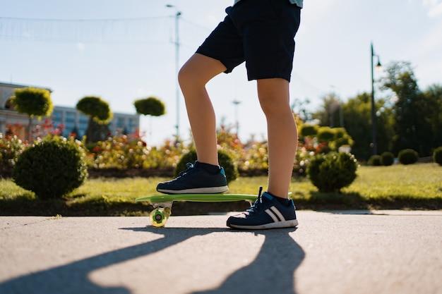 Close-up benen in blauwe sneakers rijden op groene skateboard in beweging. actieve stedelijke levensstijl van jeugd, opleiding, hobby, activiteit. actieve buitensport voor kinderen. kind skateboarden.
