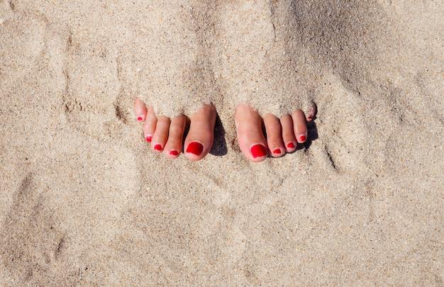 Close-up benen van gebruinde vrouw met helder zand