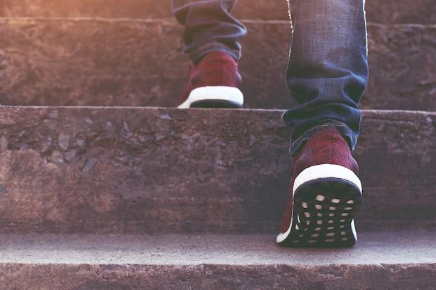 Close-up benen van jonge hipster man een persoon lopen intensivering de trap op gaan in de moderne stad, omhoog gaan, succes, opgroeien. met verkeerslijn kleur geel cross bridge viaduct.