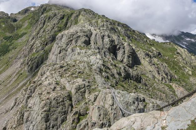 Close-up bergen scènes, lopen naar trift bridge in nationaal park zwitserland, europa. zomerlandschap, zonneschijn, dramatische bewolkte lucht en zonnige dag