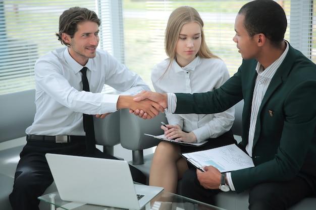 Close-up bevestigt de manager de transactie met de zakelijke handdruk van de klant