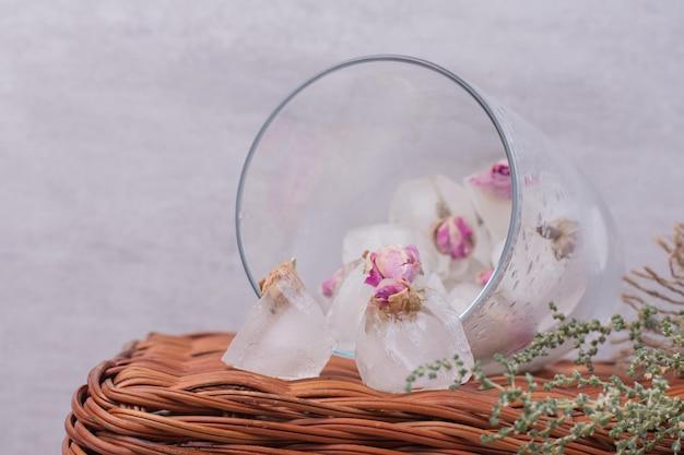 Close-up bevroren bloemen in glas op mand.