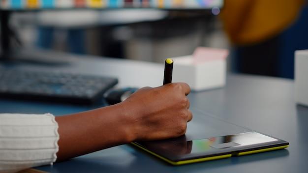 Close-up bij de hand van afrikaanse foto-editor tekenen op grafisch tablet klant foto bewerken op computer...