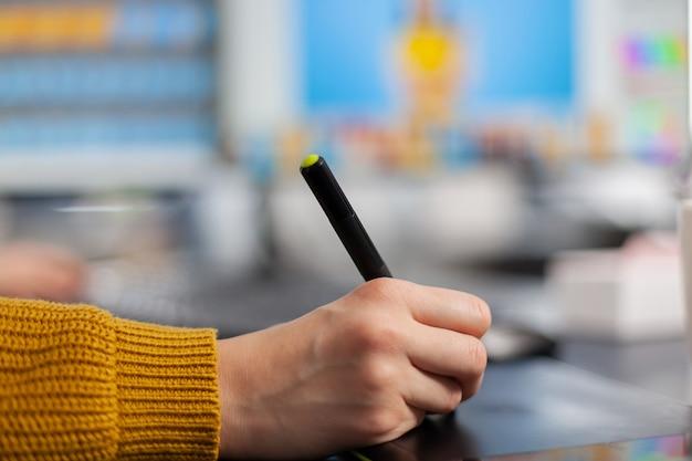 Close-up bij de hand van jonge vrouw foto-editor tekenen op grafisch tablet klant foto bewerken op computer met twee monitoren