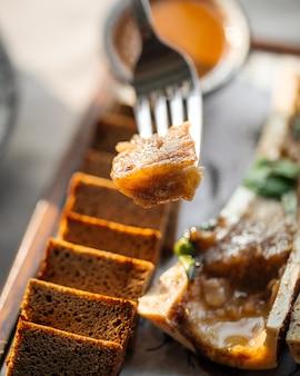 Close-up bij het eten van gastronomisch beenmerg met saus en roggebrood met bestek