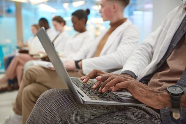 Close-up bij multi-etnische groep mensen die laboratoriumjassen dragen terwijl ze in de rij zitten en laptop gebruiken tijdens lezing over geneeskunde op de universiteit, kopieer ruimte