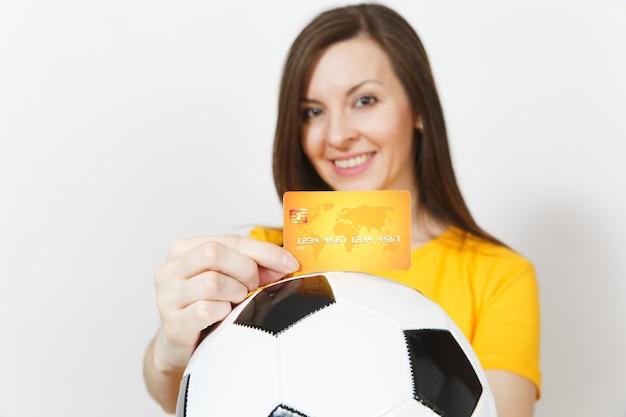 Close-up bijgesneden europese jonge vrouw, voetbalfan of speler in geel uniform met creditcard voetbal geïsoleerd op een witte achtergrond. sport, voetbalspel, opwinding lifestyle concept.