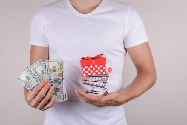 Close-up bijgesneden foto portret van blij opgewonden tevreden klant met kleine handkar met cadeautje binnen en stapel stapel geld geïsoleerd grijze achtergrond