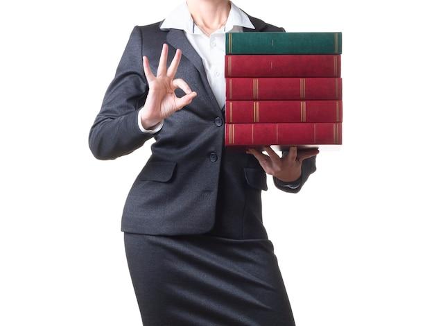 Close-up bijgesneden foto van een zakenvrouw die een stapel boeken vasthoudt en allwright-teken toont.