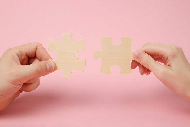 Close-up bijgesneden foto van handen die proberen te verbinden paar houten puzzelstukjes geïsoleerd op pastel roze muur achtergrond. vereniging, verbindingsconcept. kopieer ruimte reclame mock-up.