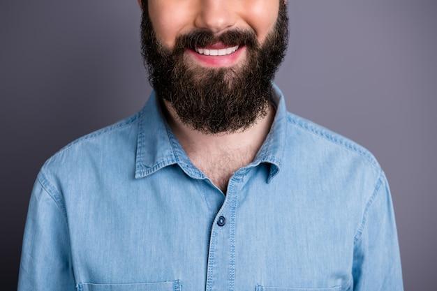 Close-up bijgesneden foto van positieve student glimlach genieten van haarverzorging spa salon procedure medisch toothy behandeling charmant gezonde kerel concept slijtage denim jeans overhemd geïsoleerde grijze kleur muur