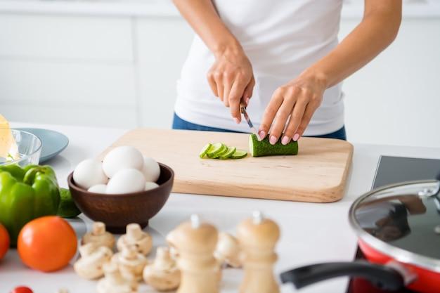 Close-up bijgesneden foto van vrolijke huisvrouw bereiden feest voor haar vegetarische familie groene biologische komkommer snijden op snijplank in witte keuken binnenshuis