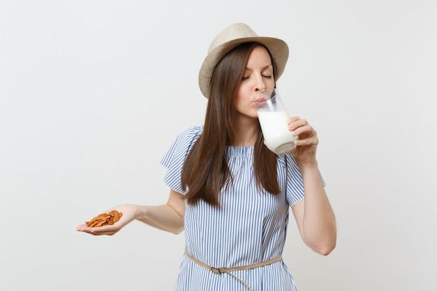 Close-up bijgesneden foto van vrouw houden in handen amandelmelk in glas, amandelnoten geïsoleerd op een witte achtergrond. goede voeding, veganistische vegetarische drank, gezonde levensstijl, dieetconcept. ruimte kopiëren.