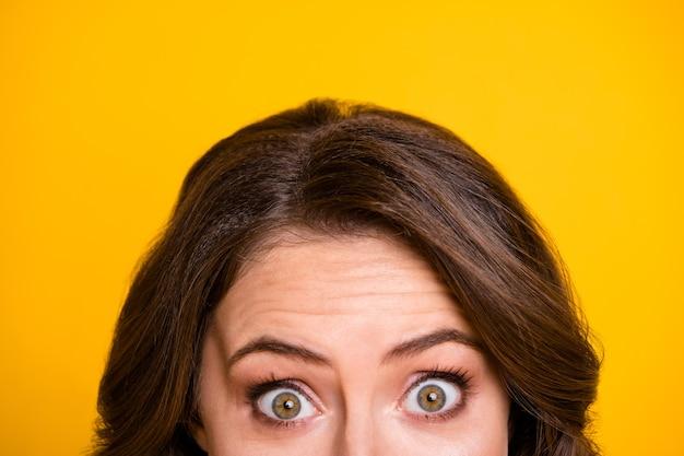 Close-up bijgesneden gezichtsuitdrukking foto van grappige doodsbange dame blik half gezicht bang ogen spelen spel verstoppertje geïsoleerde gele kleur achtergrond