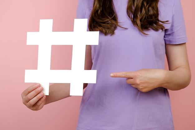 Close-up bijgesneden jonge vrouw met grote grote witte hashtag teken, virale webinhoud, internet promotie, geïsoleerd over roze kleur achtergrond in studio. bloggen blog website strategie concept