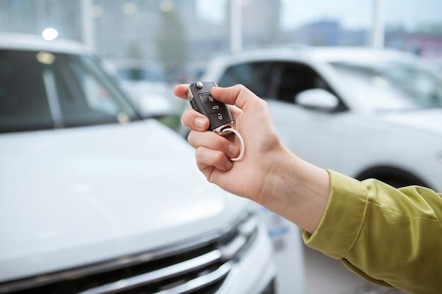Close-up bijgesneden opname van een autosleutel in de hand van de vrouwelijke bestuurder, auto's bij de dealer op de achtergrond