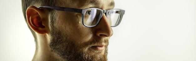 Close-up bijgesneden opname van jonge man op studiomuur