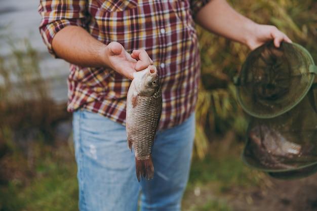 Close-up bijgesneden portret man in geruit hemd houdt in handen groen visnet en vis die hij ving op een oever van het meer in de buurt van struiken en riet. lifestyle, recreatie, vrijetijdsconcept voor vissers