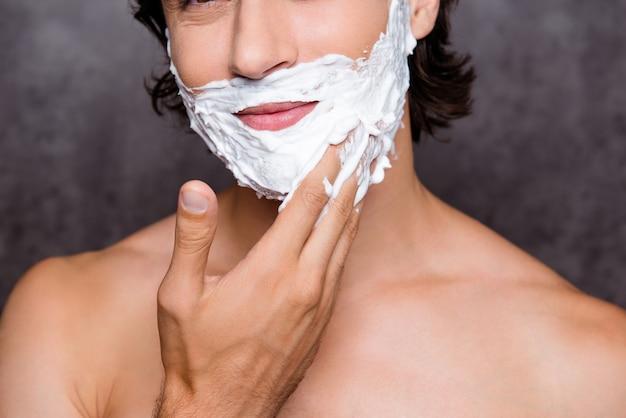 Close-up bijgesneden shot van het gezicht van vrolijke spaanse man met wit schuim