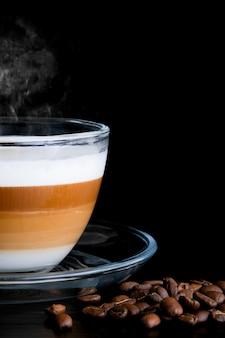 Close-up bijgesneden transparante glazen beker cappuccino met zichtbare lagen.