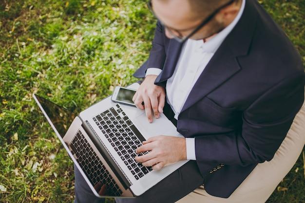 Close-up bijgesneden van handen op het toetsenbord. zakenman in klassiek pak, bril. man zit op zachte poef, werk op laptop pc-computer in stadspark op groen gazon buitenshuis. mobiel kantoorconcept. bovenaanzicht.