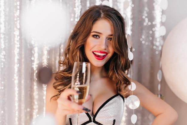 Close-up binnenfoto van schitterend donkerharig vrouwelijk model met rode lippen die glas opheffen. portret van geweldige blanke meisje vakantie vieren met champagne.