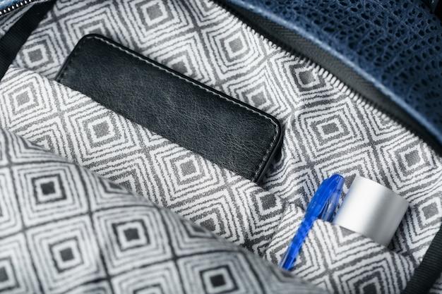 Close-up binnenzakken, elementen van een blauwe rugzak gemaakt van echt leer op donker