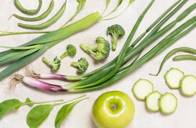 Close-up biologische groenten en appel op de tafel