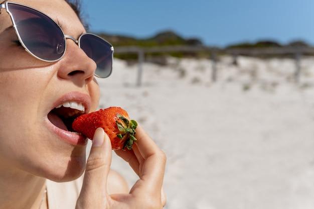 Close-up blanke vrouw die een aardbei bijt. meisje op het strand met een zonnebril.
