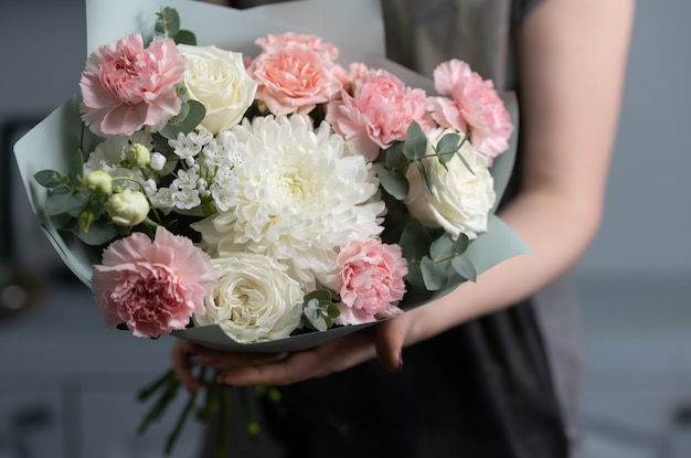 Close-up bloemen in de hand. bloemist werkplek. vrouw die een boeket met rozen, chrysant, anjer en andere bloemen schikt.