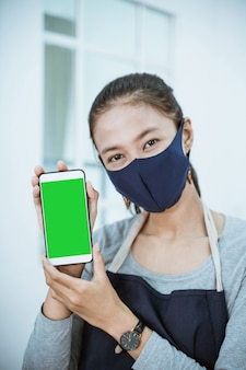 Close-up bloemist vrouw winkelier met telefoon met qris barcode betaling
