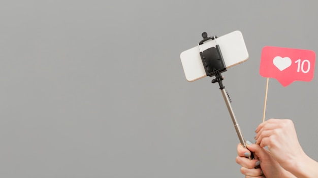 Close-up blogger selfie stick met mobiele telefoon te houden