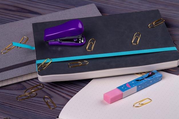 Close-up boeken met nietmachine en gum met paperclips.