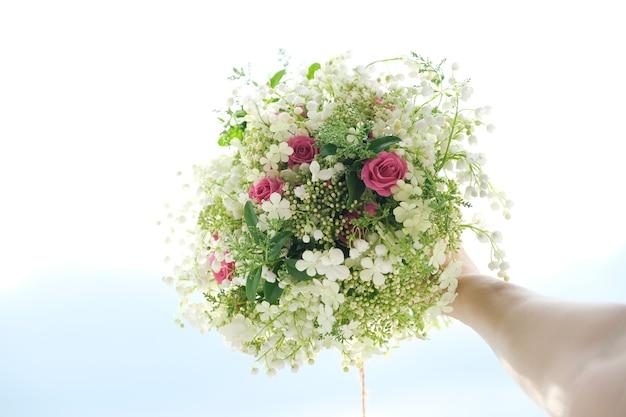 Close-up boeket van verse bloemen roos en lelietje-van-dalen in de hand van de vrouw. lente, vakantie, bruiloft, schoonheid