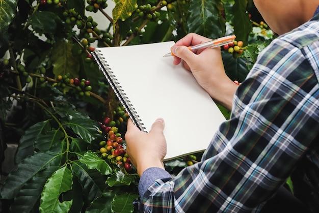 Close-up boer neemt notities met een pen op een notitieboekje in coffee farms plantations